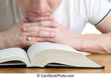 Man praying with the Bible. Focus on the Bible
