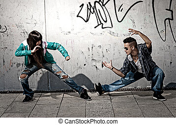 Young urban couple dancers hip hop dancing fight acting...