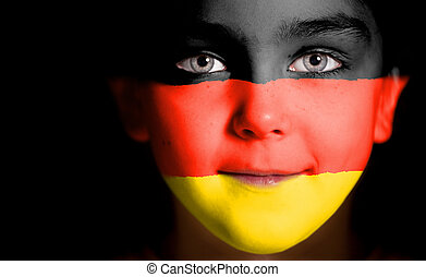 Child face painted with the flag of Germany. Closeup