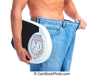 Happy Fitness man with a scales. Isolated on white...