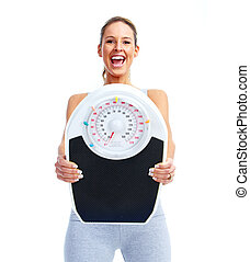 Happy Fitness woman with a scales. Isolated on white...