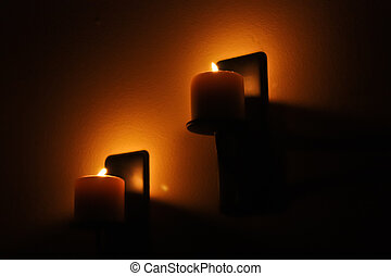 Candle Light - Two burning candles mounted on the wall.