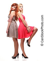 Two pretty women ginger with blonde in gowns on white