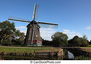 Ancient windmill on coast of a small pond