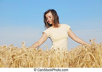 Young woman touching grain
