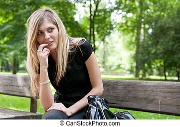 Flirt - Young woman siting on bench - Portrait of young...