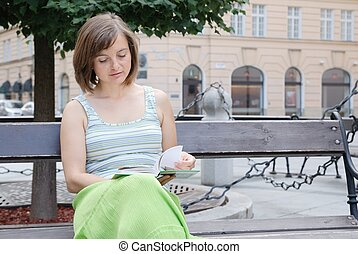 Reading on street - Young woman dressed in green reads book...