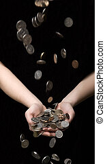 Raining coins in hands towards black background