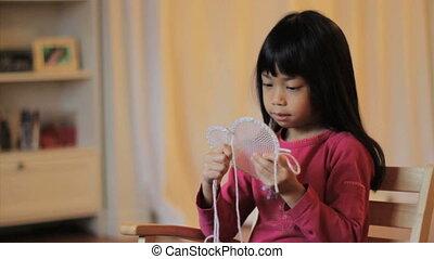 Girl Stitching A Heart Shape Design
