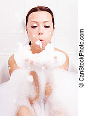 woman taking a bath - beautiful young brunette woman taking...