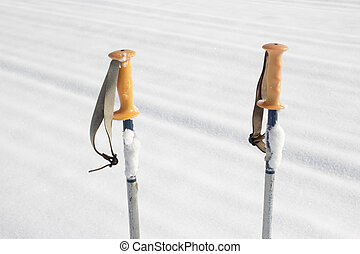 ski poles in the snow - clos up of an old pair of ski poles...