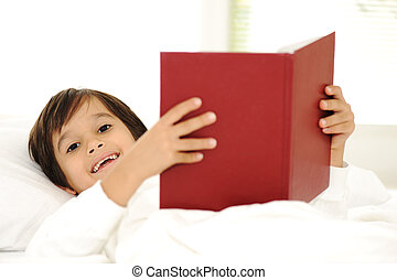 Kid reading book in bed