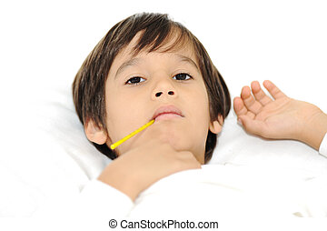 Sick little boy with thermometer, laying on bed