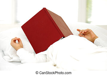 Kid reading book in bed, falling asleep