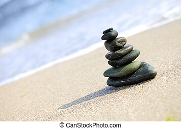 Stack of sea pebbles on the beach. Shallow depth of field.