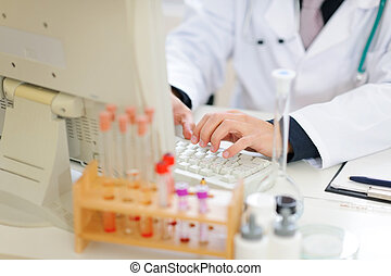Closeup on hands of medical doctor working on pc