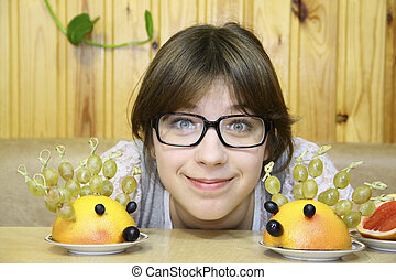 The cheerful girl and ridiculous hedgehogs from fruit on a table