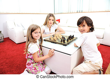 Happy family at home, young mother playing chess with her children