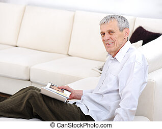 Elderly man relaxed, reading book  in living room