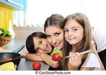 Happy children with their mother in the kitchen together