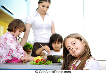 Happy family in the kitchen, mother and children cooking together