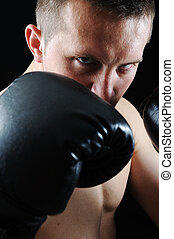 Artistic portrait of attractive boxer against black...
