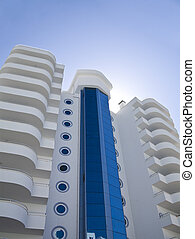 luxury white residential building with balconies on a background blue sky