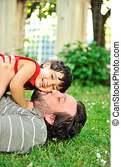 Father and son in park playing on ground, kissing - Father...