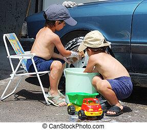 Two little boys washing car