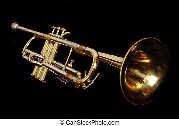 old gold trumpet isolated on the black background
