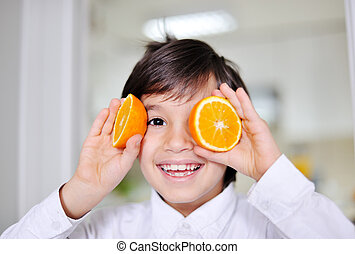Little boy playing with orange slices on eyes as glasses