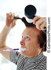 Senior woman drying hair with fan and brushing teeth