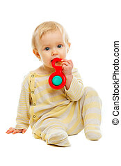 Lovely baby playing with rattle on floor isolated on white