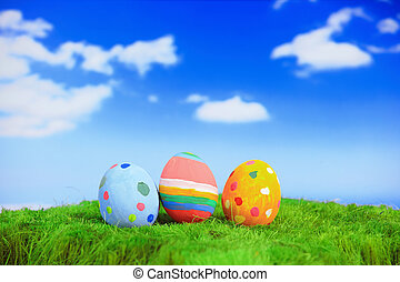 Easter eggs on grass with blue sky and cloud background