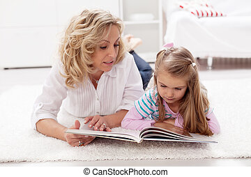 Story telling time - woman and child reading a tale book at...