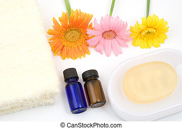 Essential oil and bath supplies with gerbera daisy on white...