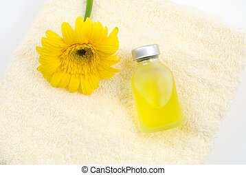 Essential oil on the yellow towel with gerbera daisy