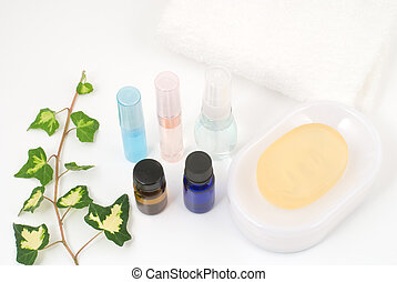 Essential oil and bath supplies with ivy on white background