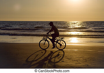 Biker silhouette at sunset 2 - GOA, INDIA - 01 DEC 2011:...