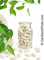 Herbal supplement pills and fresh leaves