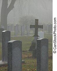 Cross among headstones in fog