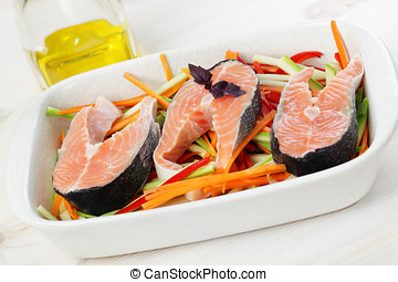 Raw salmon steaks with vegetables