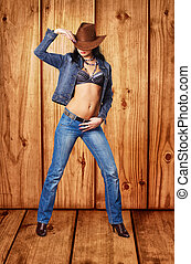 Girl in jeans and a cowboy hat on wooden background