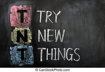 Acronym of TNT for Try New Things written in chalk on a...