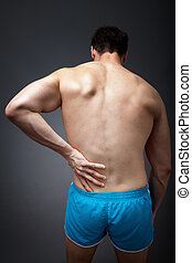 Back pain concept - man holding his sore torso