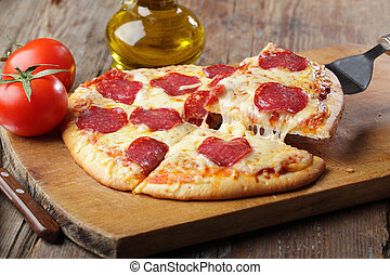 Pepperoni pizza - Pizza with salami and cheese on a cutting...
