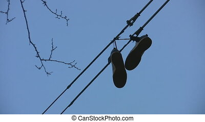 Sneakers hanging from wire. - Pair of sneakers hanging from...