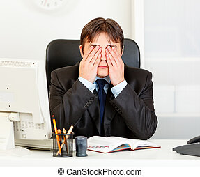 Modern business man sitting at office desk and making see no evil gesture