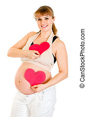 Happy pregnant woman holding two paper hearts in hands...