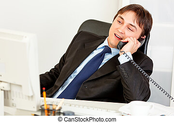 Pleased businessman sitting at office desk and talking on...